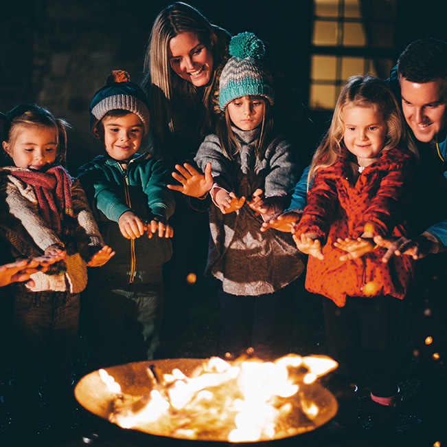 Family with children surrounded by a fire pit