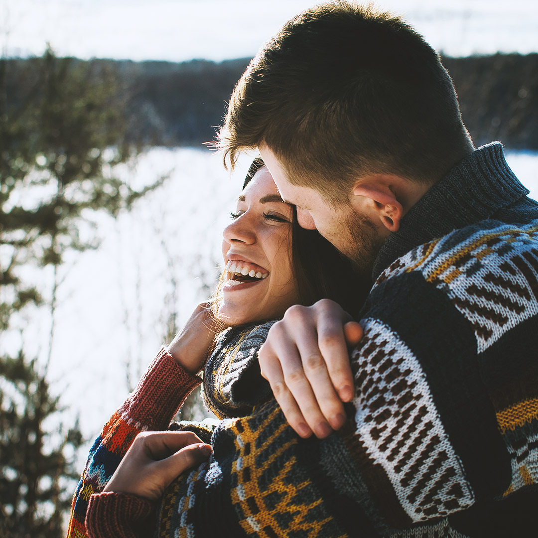 Cheerful couple embracing wearing sweaters