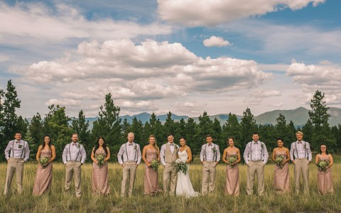 wedding party gathered for pictures against an open field