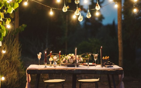view of a reception table at night below string lights