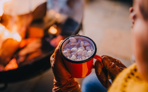 view of hand holding a cup of hot cocoa with marshmallows