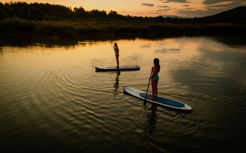 girl and boy paddleboarding on a lake at sunset