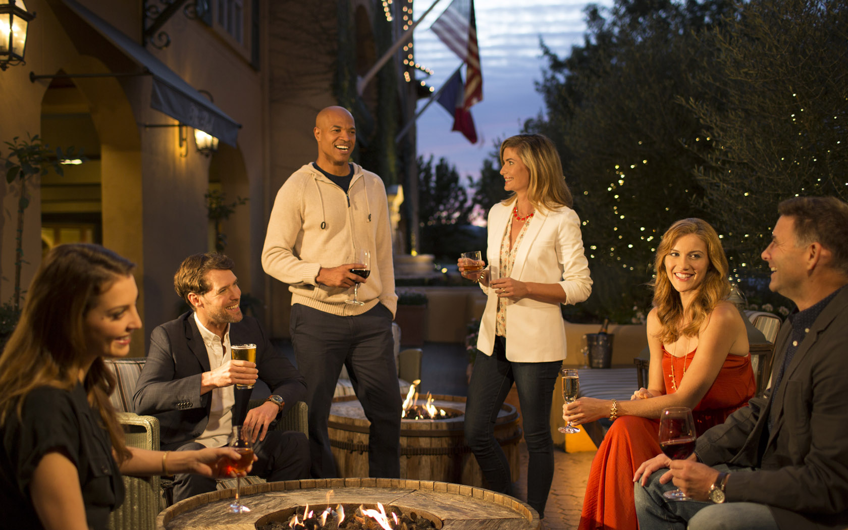 people having drinks around a firepit