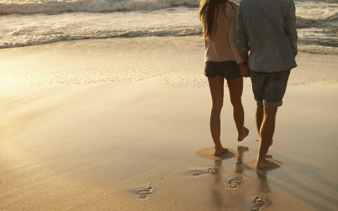 couple holding hands walking at the beach