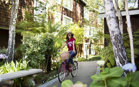 woman wearing a stanford shirt riding bicycle