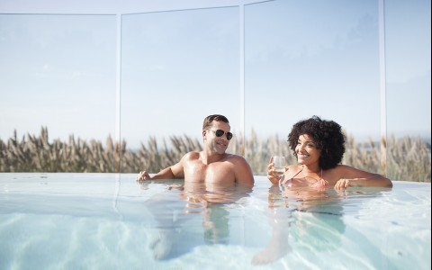 couple enjoying a glass of wine in the pool