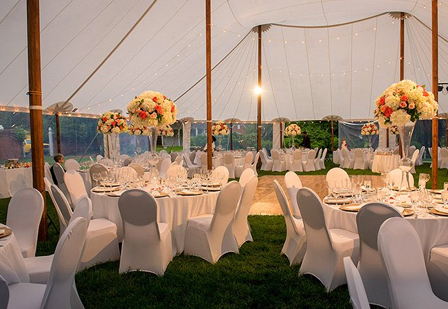 Wedding reception set up with circular tables outside under white tent