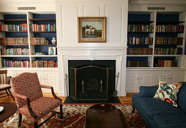 Living space with seating, book shelves, white cabinets & fireplace