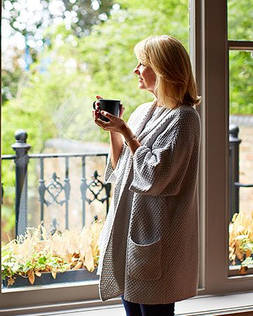 Woman in oversized sweater drinking coffee as she looks out window