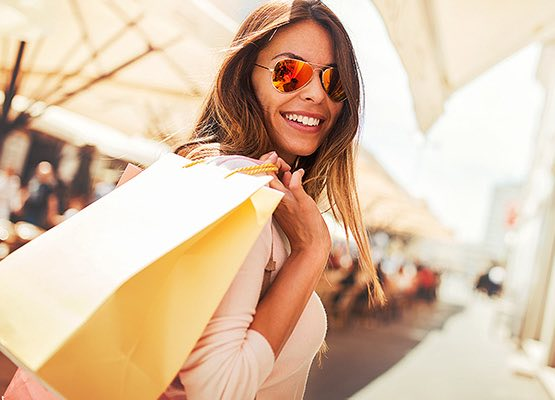 Woman wearing sunglasses holding a shopping bag
