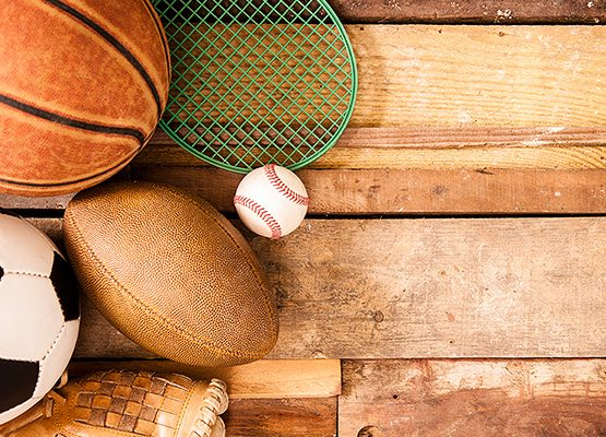 soccer ball, football, basketball, baseball and tennis racket placed on a wood floor