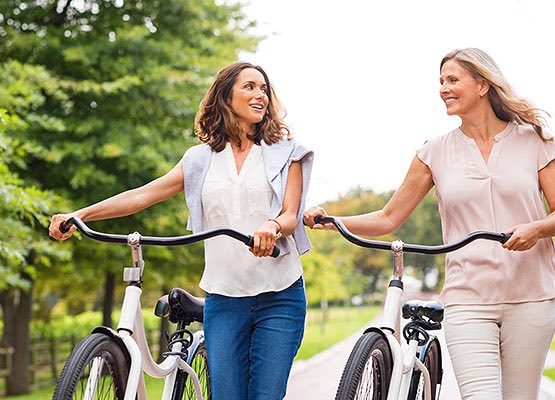 two woman walking with their bikes