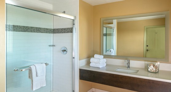 bathroom with glass shower and tan walls