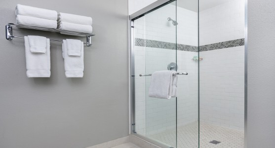 glass shower with white towels