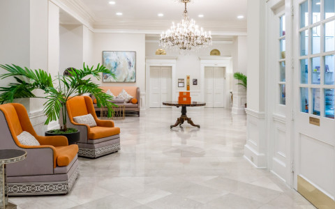 hotel lobby area with white floors and walls, orange chair, brown and orange couch, and round table in center of room