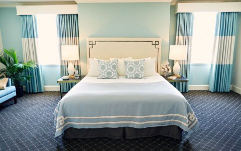 guest room with white and light blue colors, bed and two nightstands
