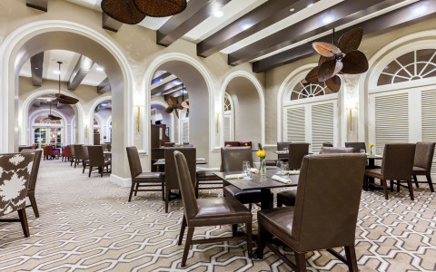 restaurant dining area with brown tables and chairs and arched columns