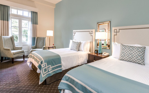 two white linen beds with light blue quilts at the end of the bed
