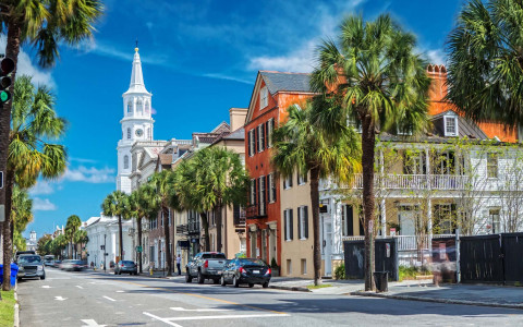 a street with colorful houses and a white steeple church in charleston