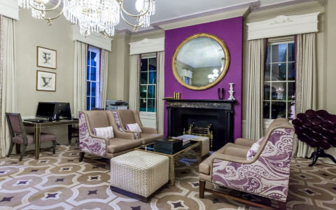 lounge room with a purple colored wall with fireplace, couches and chairs