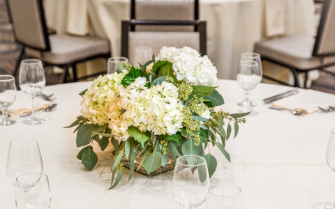 floral centerpiece on a table with white flowers and greenery
