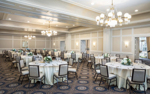 event space set up with white linen draped tables, chairs, and flower centerpieces