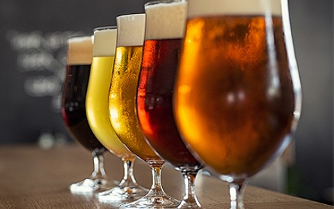 a row of various colored beers in glasses