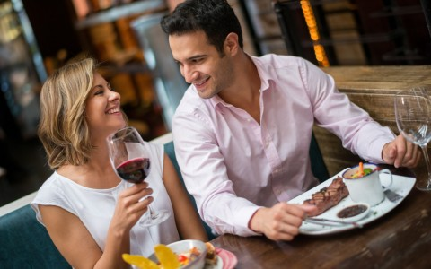 man and woman enjoying dinner and drinks together