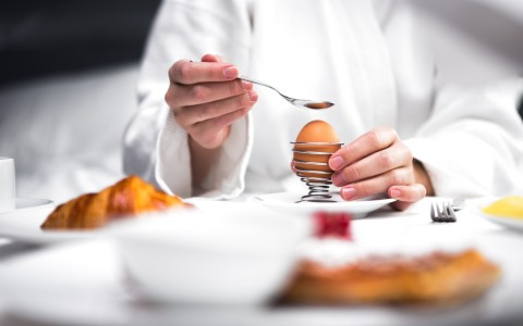 a chef drizzling sauce over an egg