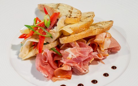 a plate of deli meats and bread