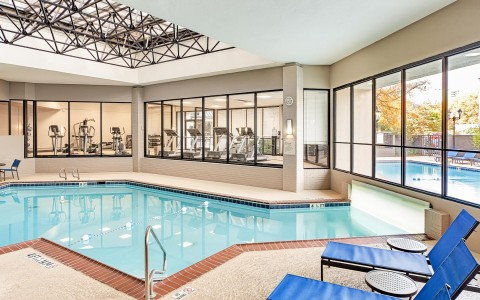 indoor pool at the hotel with a view of the exercise room and a view of the outdoor pool area