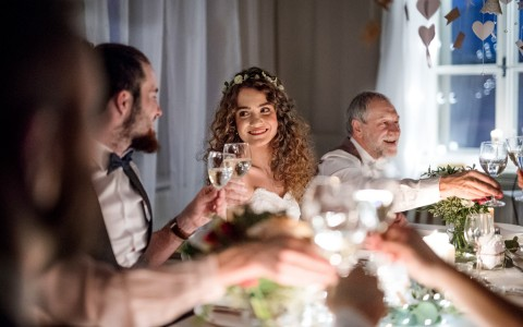 bride and groom toast each other while sitting at the dinner table