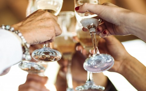 group of friends bringing their champagne glasses together for a toast