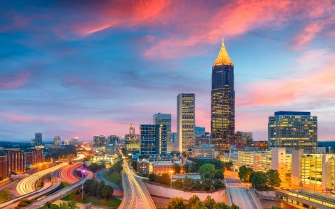 a view of downtown atlanta with pink and blue skies at sunset