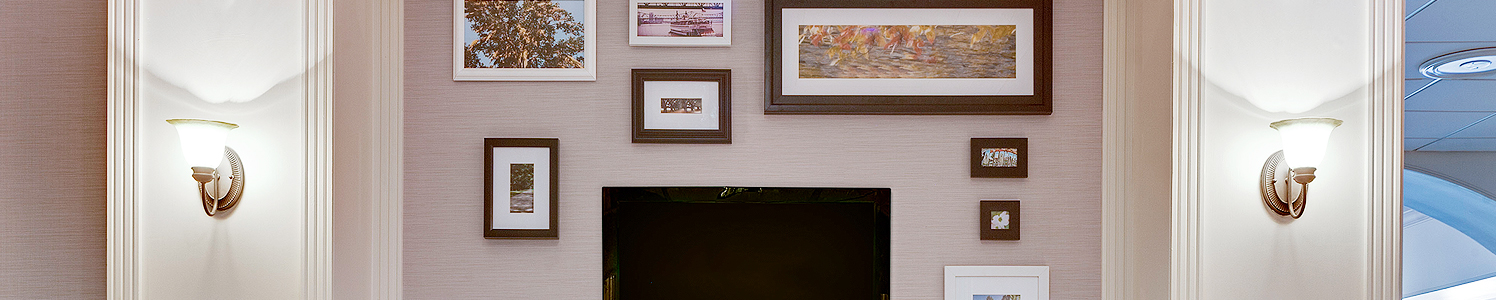 a wall with various sized picture frames and a tv on the wall