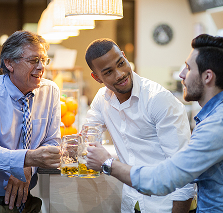 a group of three male friends enjoying drinks after work
