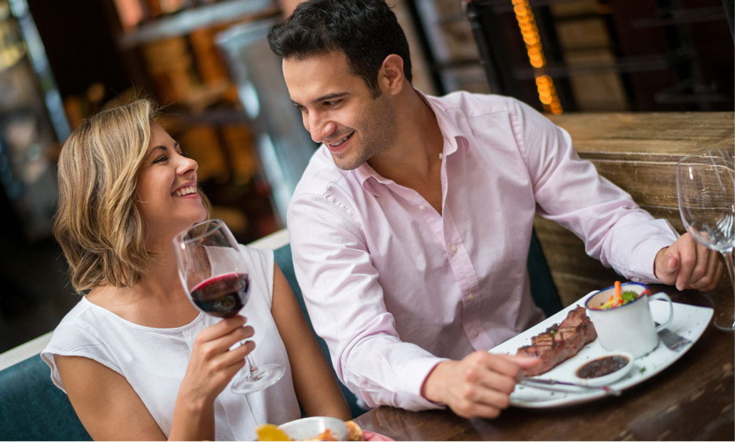 man and woman having dinner and drinks at a restaurant
