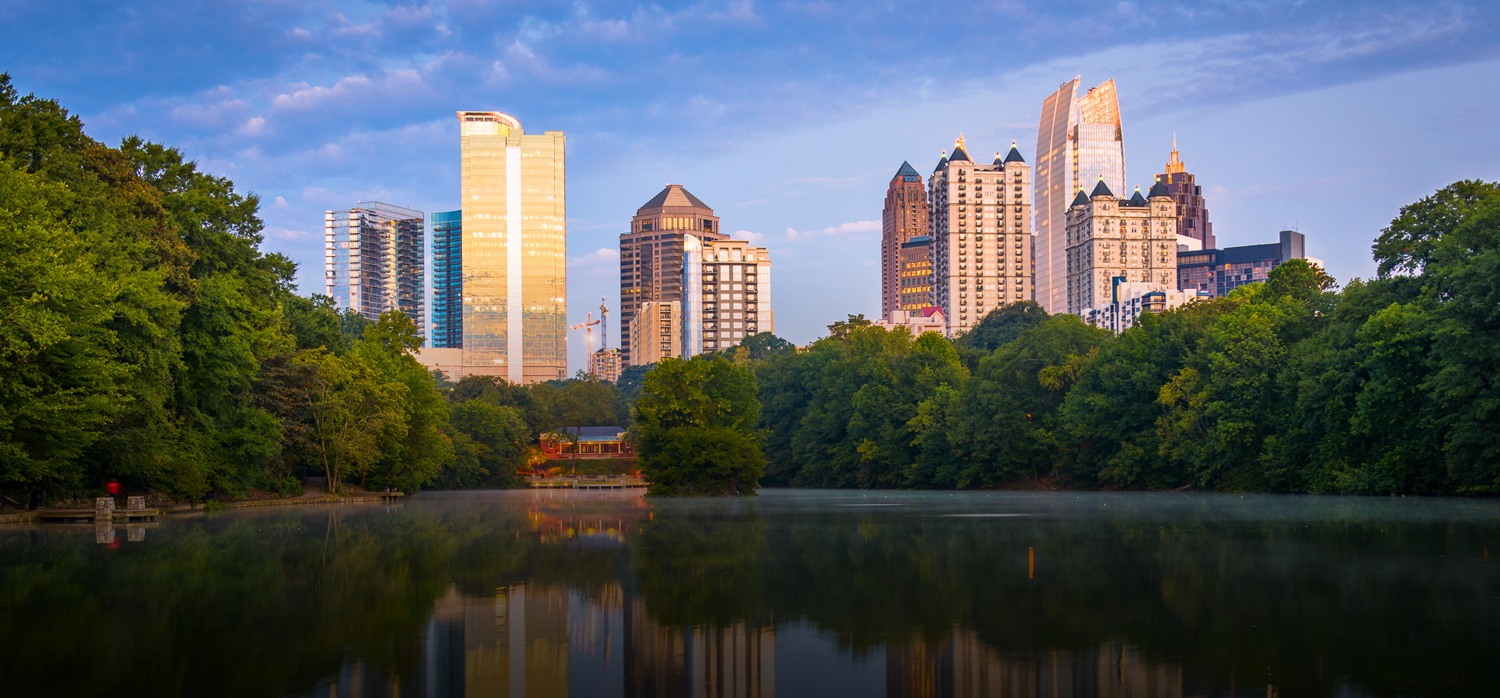 a view of downtown atlanta buildings seen in the distance from behind a pond and trees