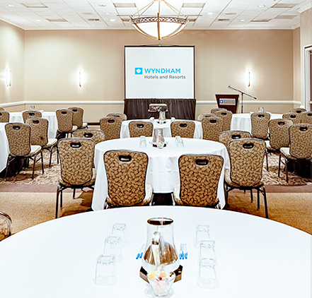 event space set up with round tables and chairs facing a projector screen and podium