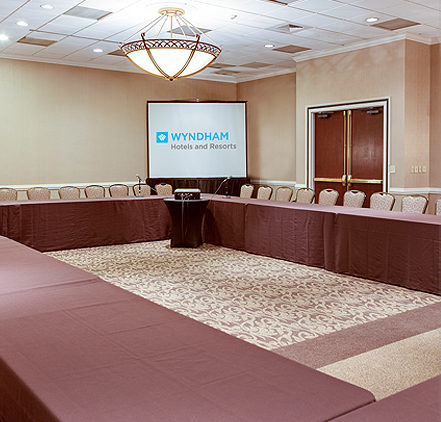 event space with a u-shaped conference table and a projector screen in the corner of the room