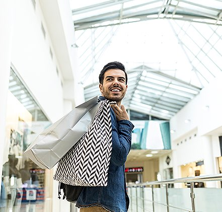 a man at the shopping mall holding a bag over his shoulder