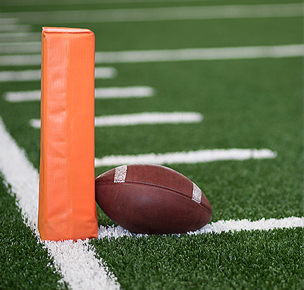 football laying on a field next to an orange position marker