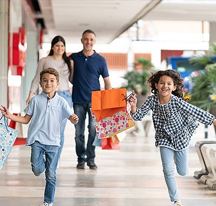 two children holding shopping bags running in front of their parents at the mall