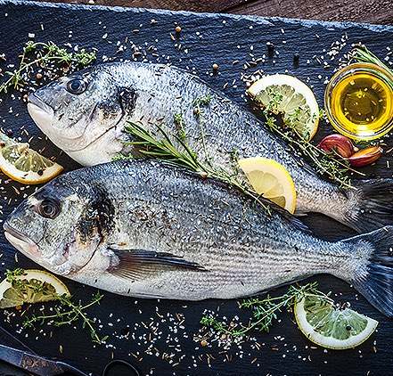 two fish on a black platter seasoned with salt, lemon slices, and herbs