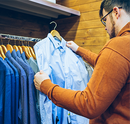 a man at a clothing store looking at a blue button up shirt