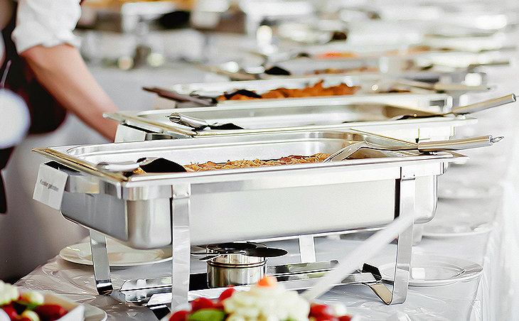 a long table of metal catering pans filled with food at a wedding reception