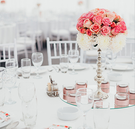 a table decorated fro a wedding with a white and pink floral centerpiece