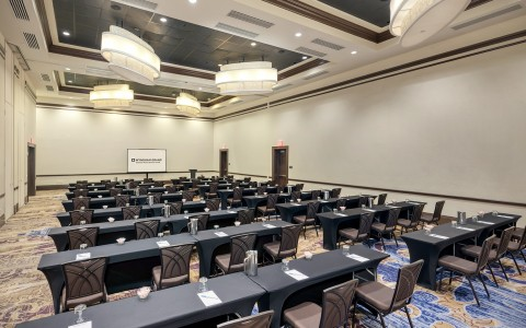 a larger conference room made for panel discussions with long horizontal tables facing a projector screen