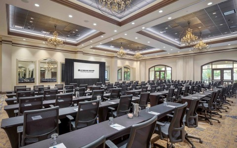 a large meeting room with unique chandeliers hanging from the ceiling