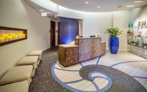 the lobby of a spa with blue tones and a swirl pattern on the floor